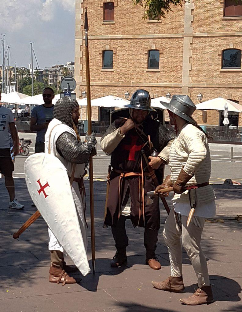 Tres recreacionistes conversen amb el Museu d'Història de Catalunya al fons.