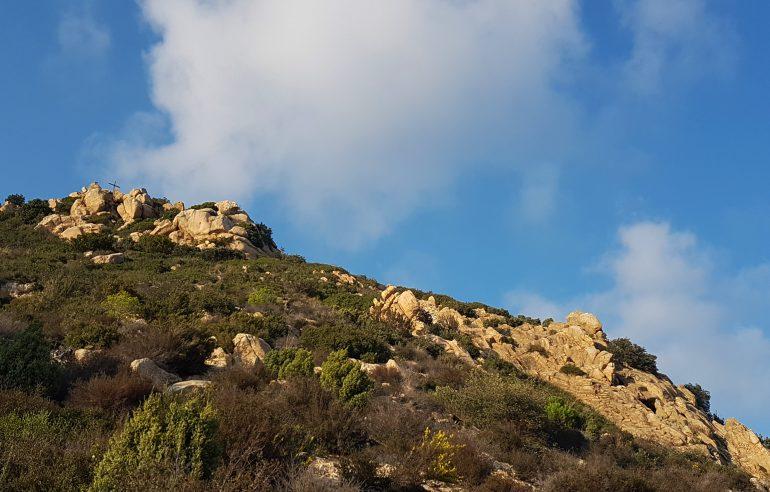 Creu del Montcabrer al cim, a la dreta, i la Cova de les Bones Dones a sota, a l'esquerra